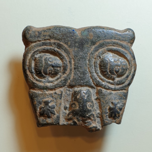 A bronze buckle in a shape of owl depicts Peter